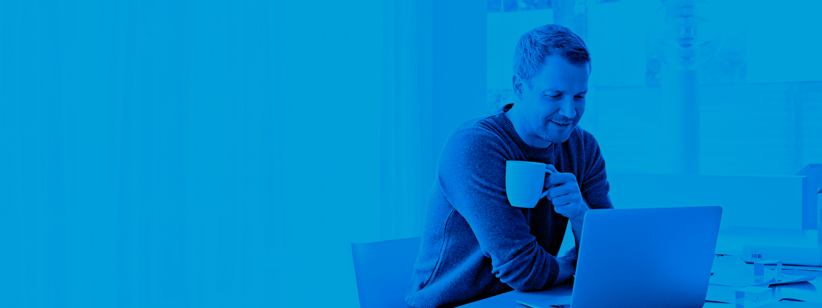 Image of man drinking coffee while he works