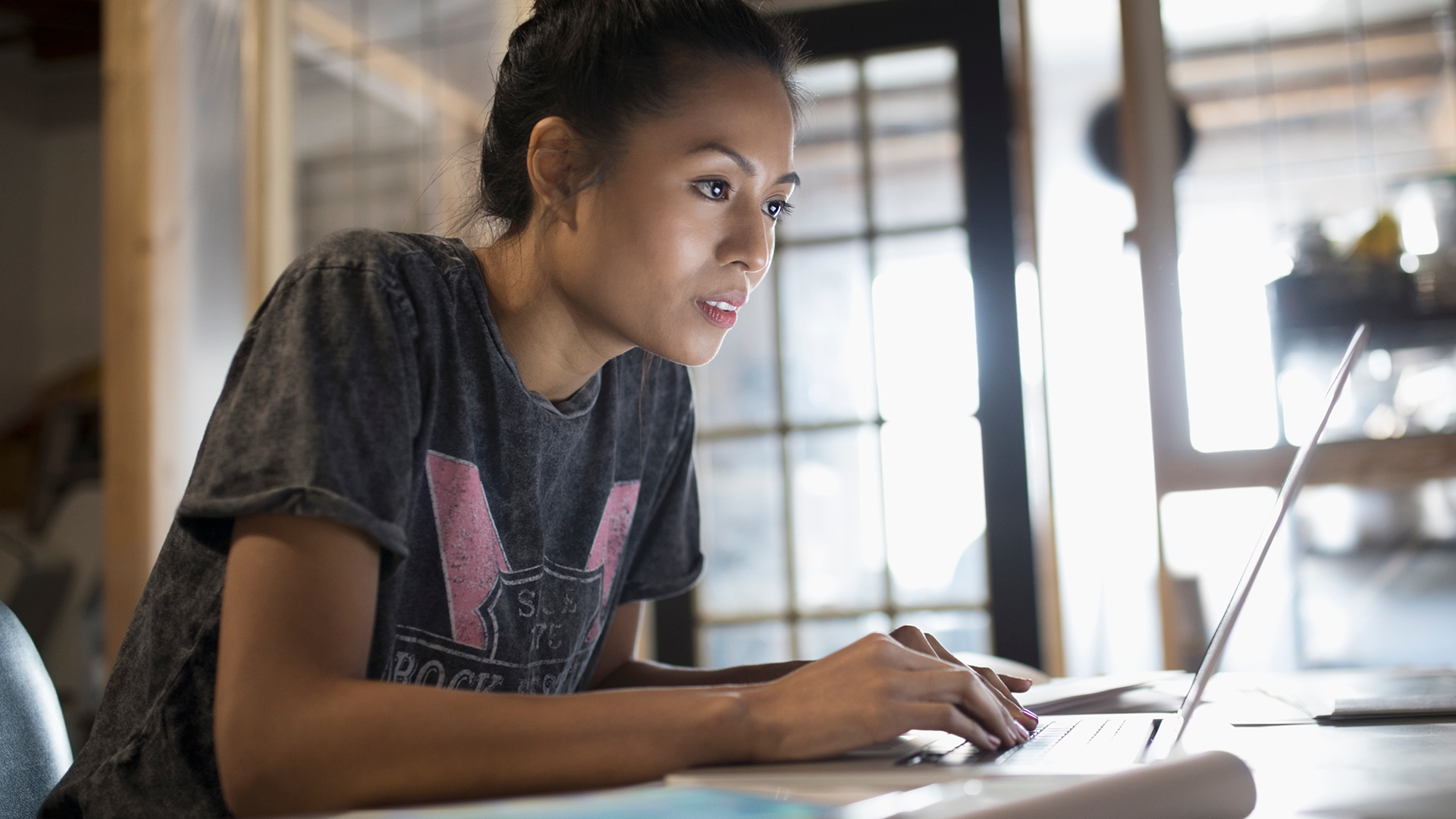 Image of a woman working at a laptop