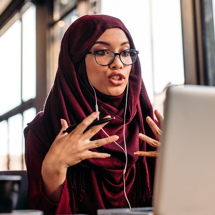Image of a woman talking on a headset in front of a laptop